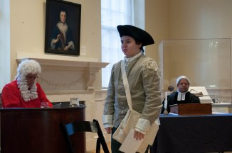 "Boston- March 5th, 2016- A young member of the audience joins Paul Summers (L) and Mike LePage (R) in the interactive play ""Trial of the Century"". The play is a part of the Old State House's program in commemoration of the Boston Massacre. (Marwa Morgan/BUNS)"